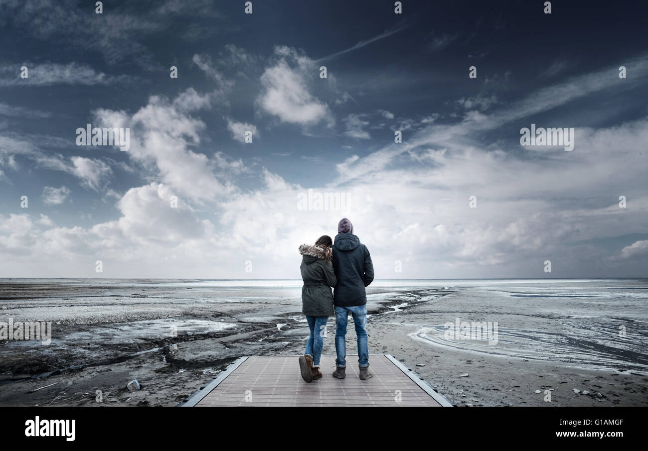 Romantic young couple on a pier looking away, back view, lake and mountains on background - Stock Image