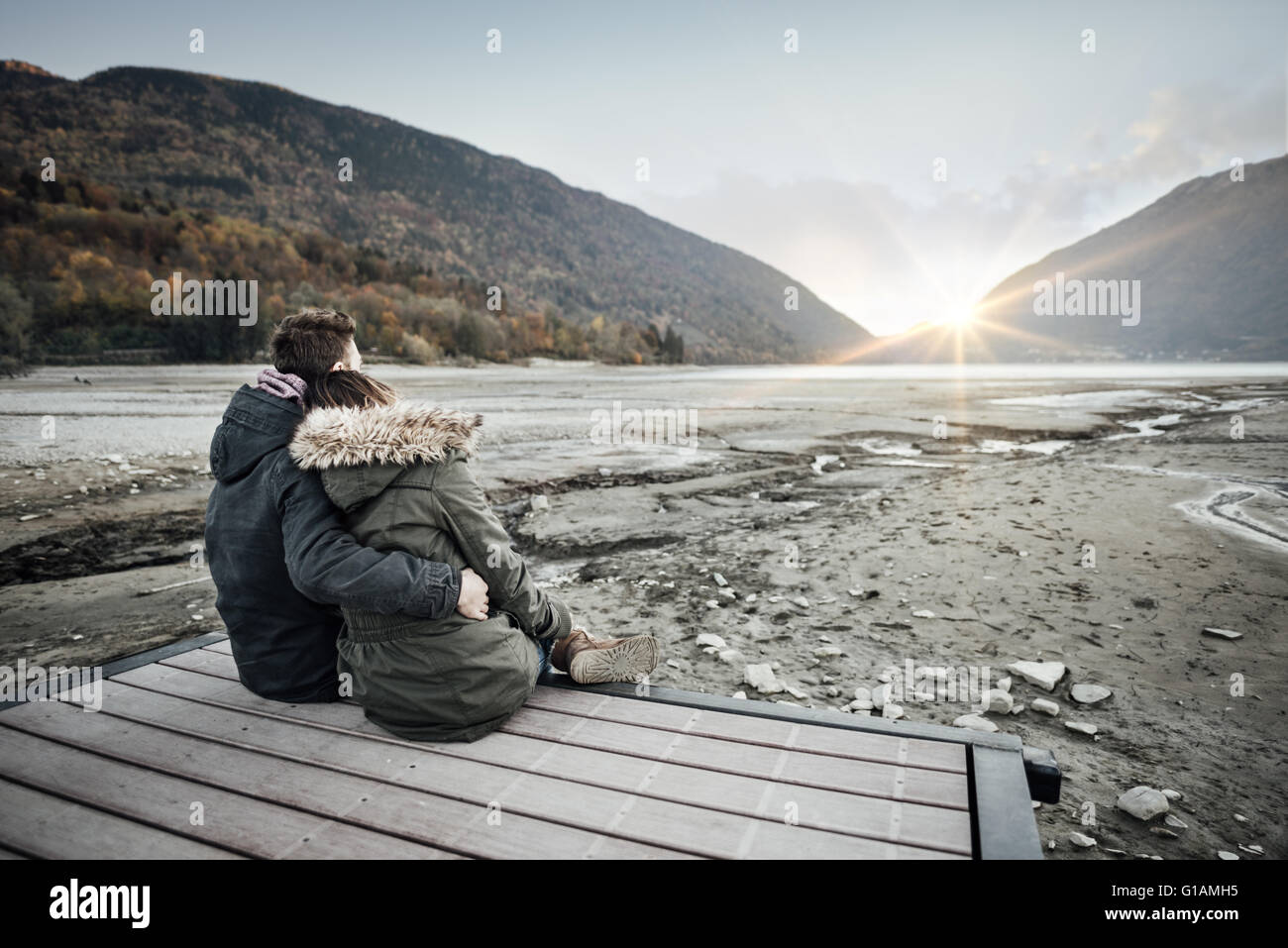 Loving couple sitting on a pier, hugging and looking away, love and feelings concept - Stock Image
