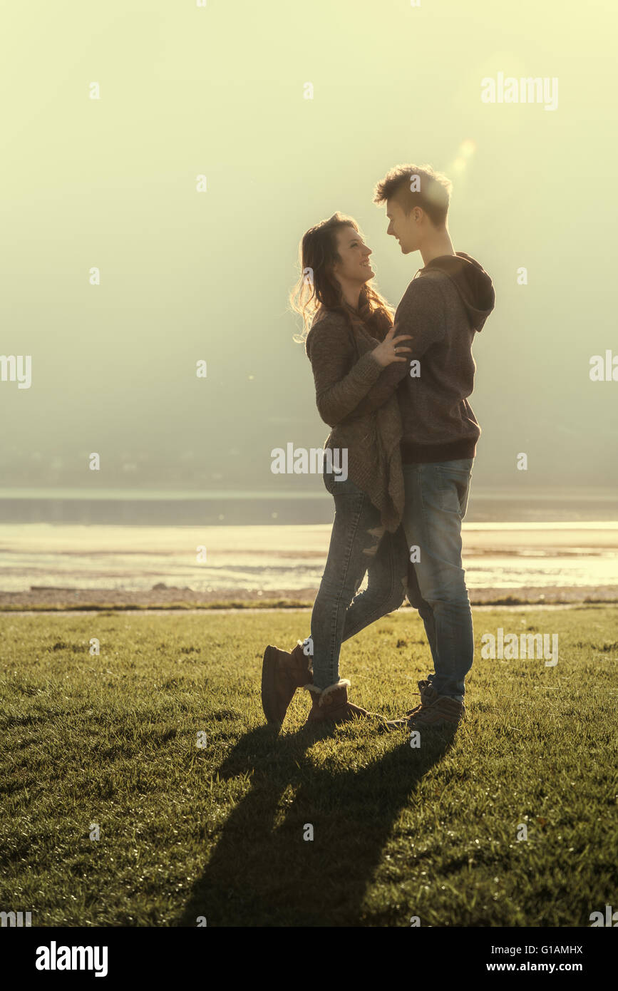 Happy romantic loving couple at the lake hugging and staring at each other, love and relationships concept - Stock Image