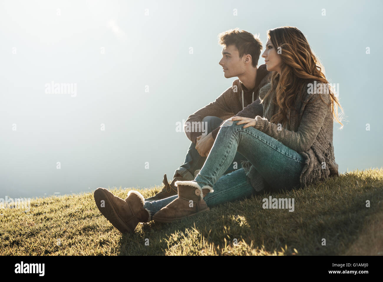 Smiling young couple sitting on grass during a sunny day, looking away and dreaming about their future - Stock Image