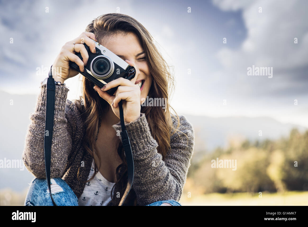 Young female photographer sitting on the grass and taking pictures, natural landscape on background - Stock Image