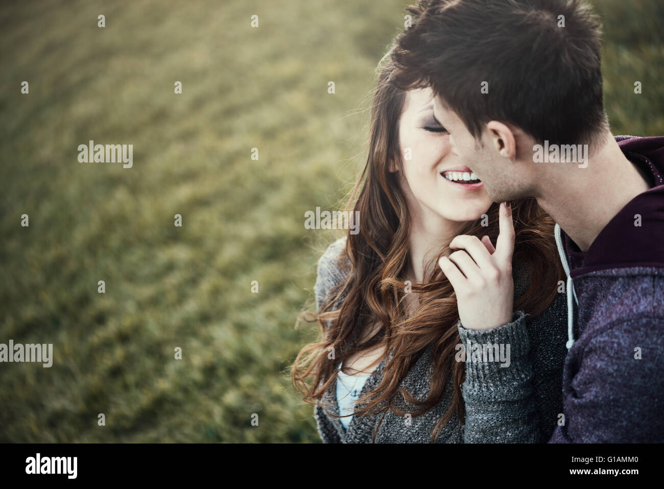 Young loving couple sitting on grass, she is flirting with him, love and relationships concept - Stock Image