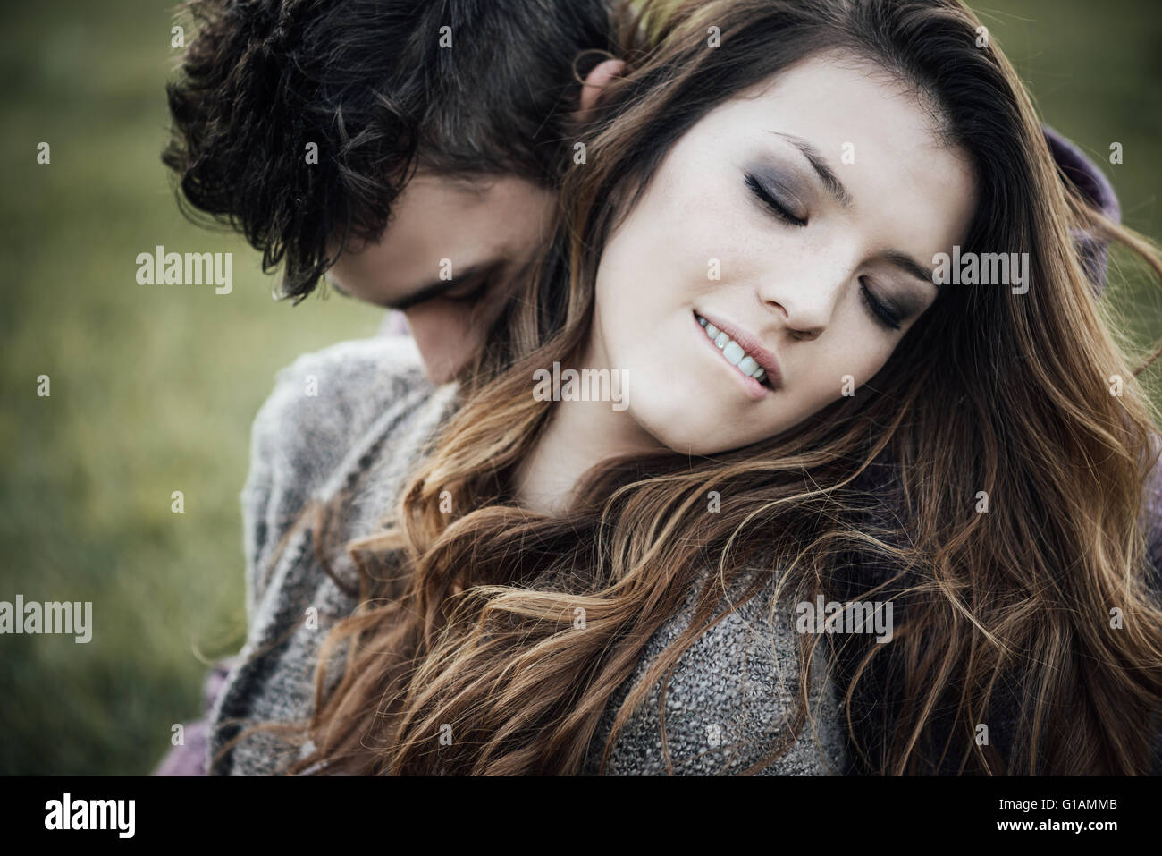 Romantic couple outdoors, they are sitting on grass and hugging, she is biting her lip - Stock Image