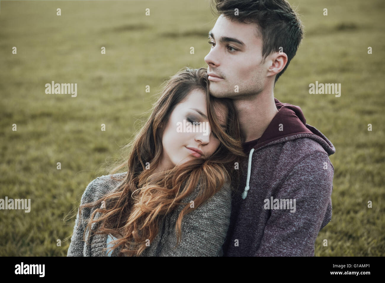 Young teenagers outdoors, sitting on the grass and cuddling, he is hugging his girlfriend, relationships and feelings - Stock Image