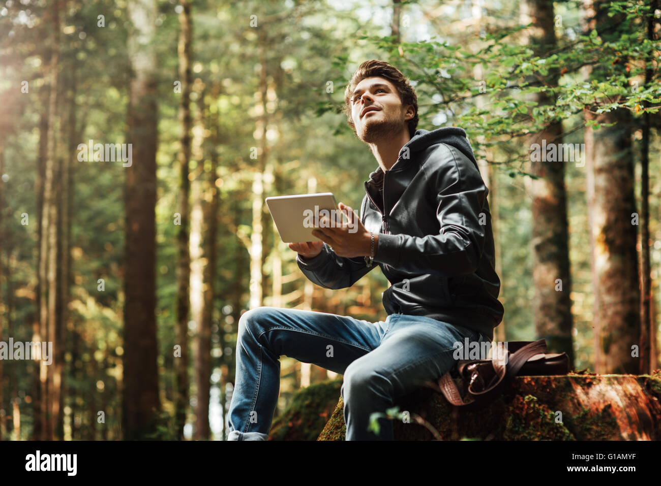 Young handsome man sitting in the woods and using a digital touch screen tablet, wi-fi connection and freedom concept - Stock Image