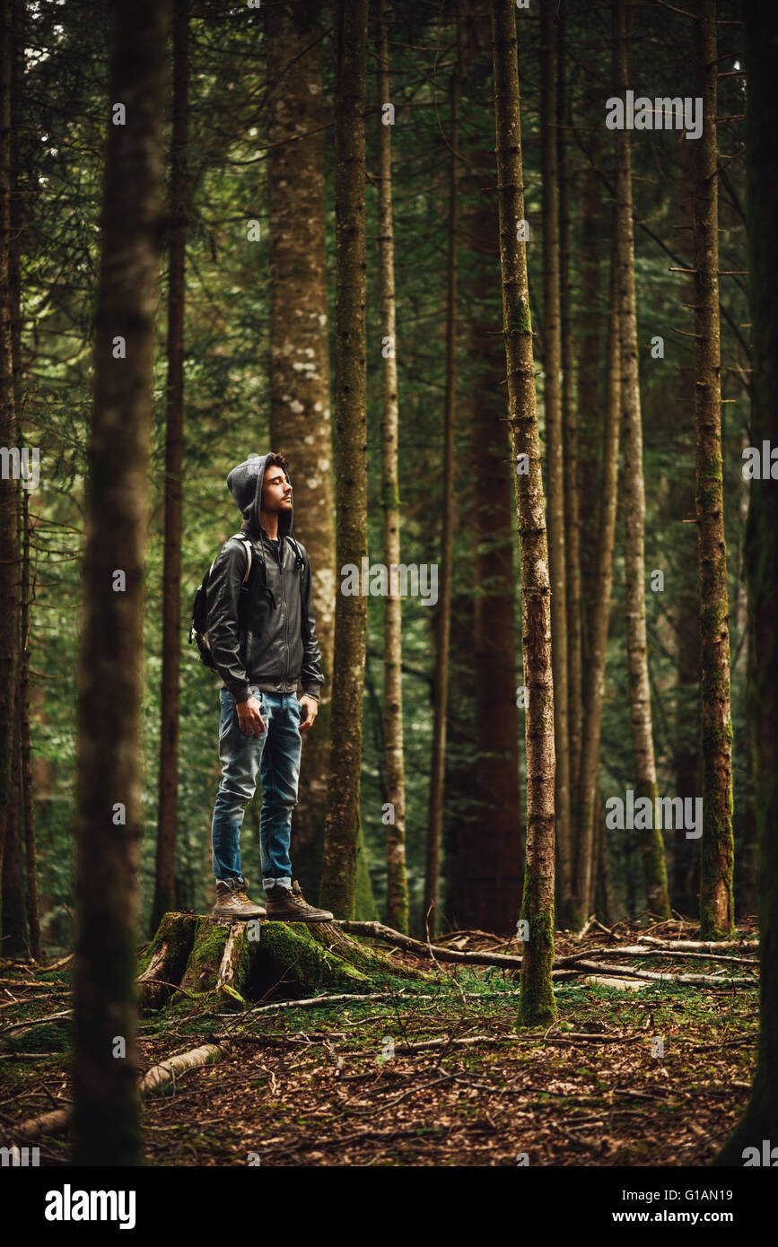 Hooded young man standing in the forest and exploring, freedom and nature concept - Stock Image
