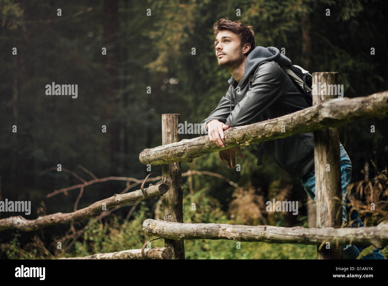 Young man with backpack hiking in the forest and leaning on a wooden fence, nature and physical exercise concept - Stock Image