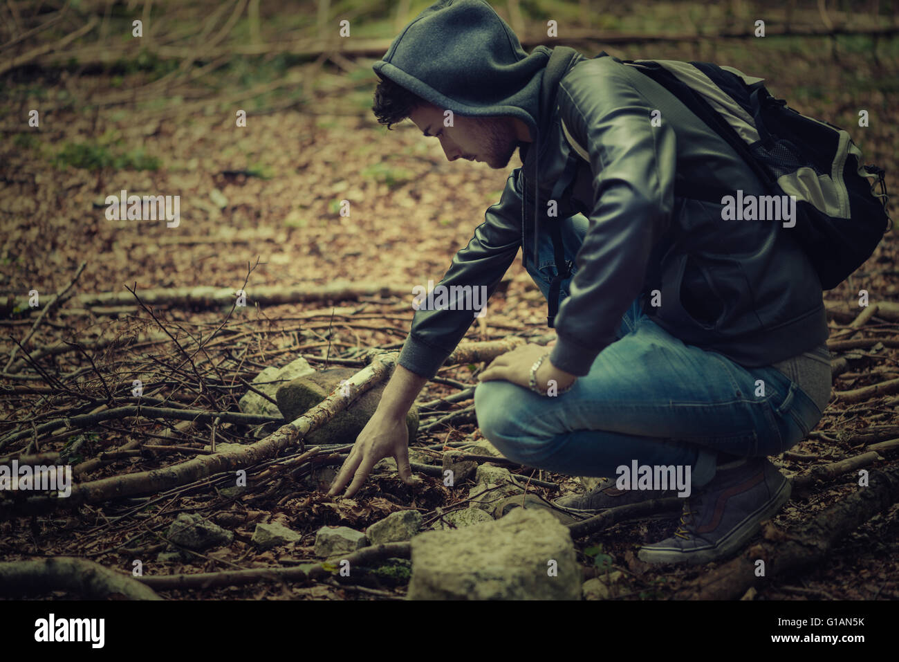 Man in the forest exploring and searching for tracks, adventure and freedom concept - Stock Image