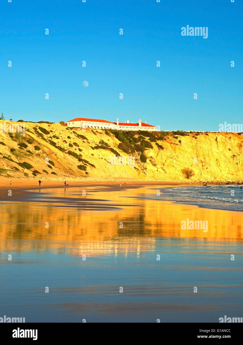 People on the ocean beach at sunset. Full moon in the sky.  Portugal - Stock Image