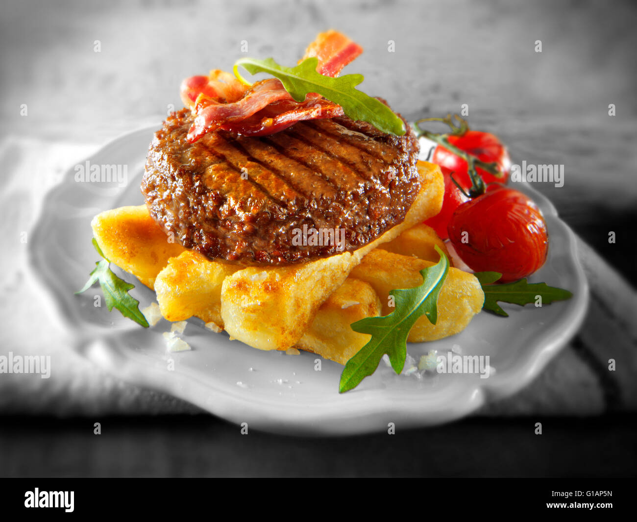 Char grilled beef burger or hamburger and bacon with chunky chips and salad - Stock Image