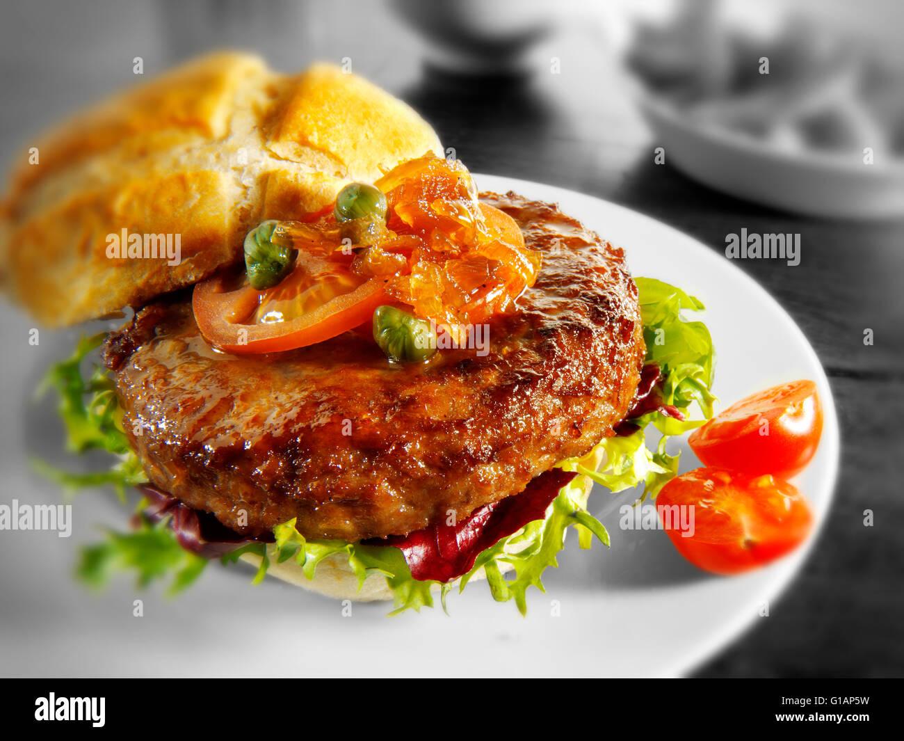 Hamburger or beef burger in a bun with relish and salad - Stock Image