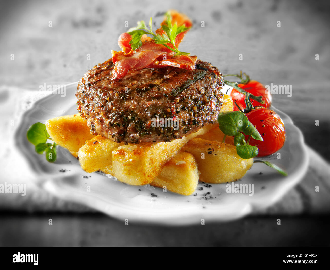 Cooked Peppered beef burger or hamburger with bacon and chunky chips - Stock Image