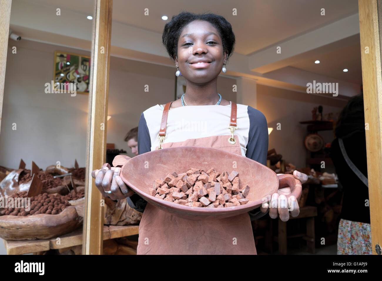 Young woman at Dark Sugar chocolate cocoa shop making handmade artisan chocolates in Brick Lane, East London UK - Stock Image