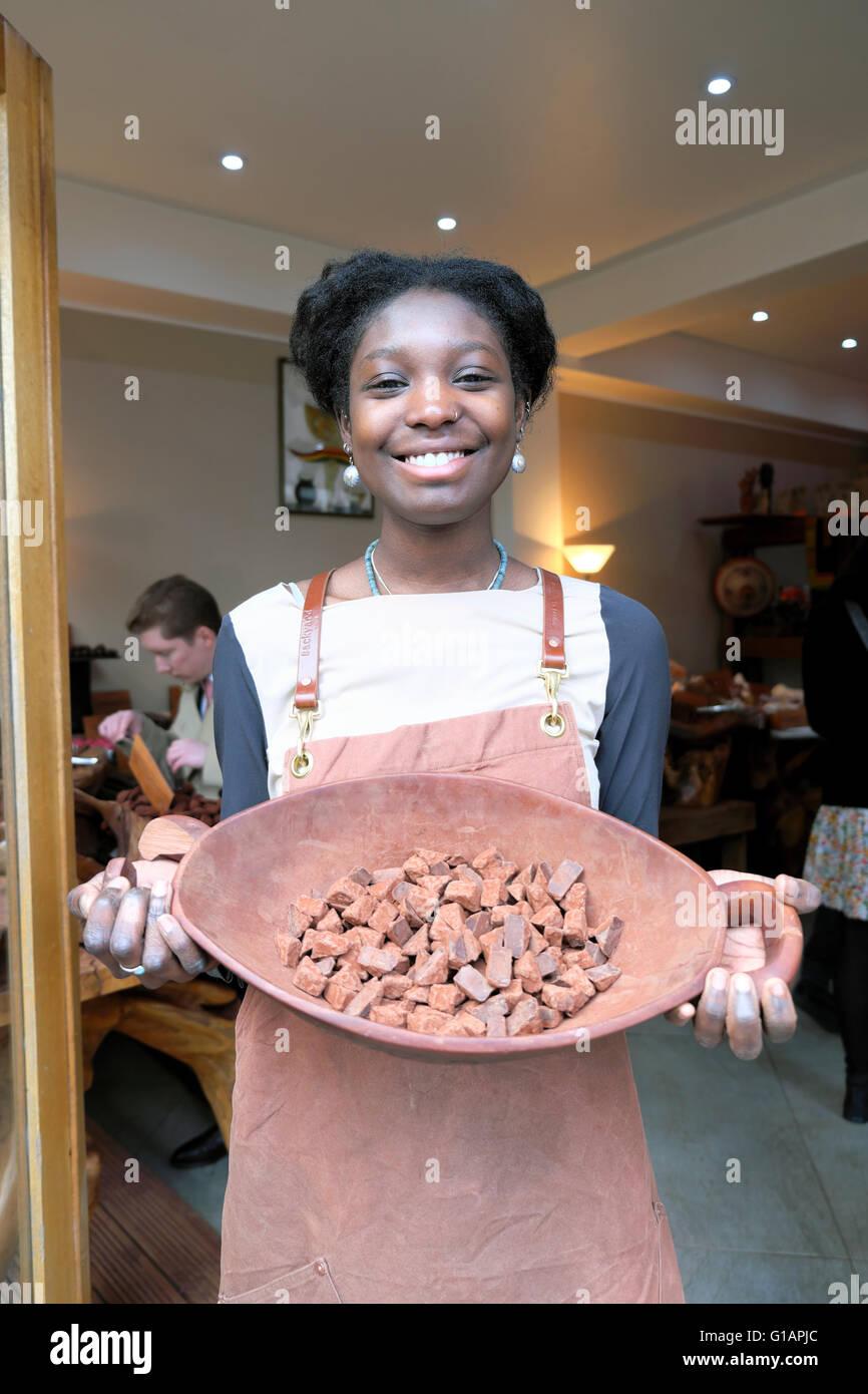 Young woman at Dark Sugars chocolate cocoa shop making handmade artisan chocolates in Brick Lane, East London UK - Stock Image