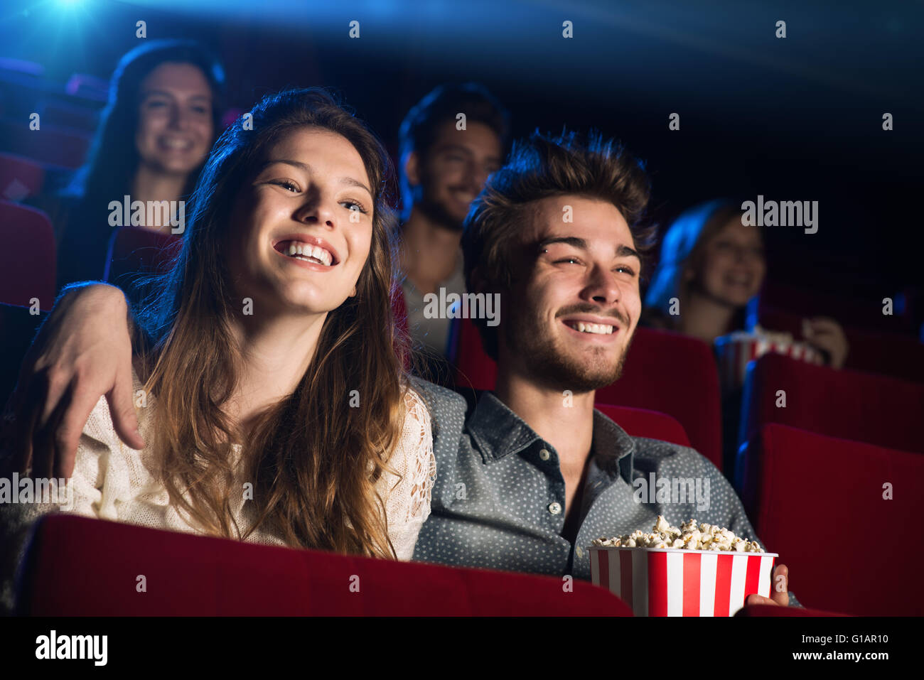 Young loving couple at the cinema watching a movie and smiling, people sitting on background - Stock Image