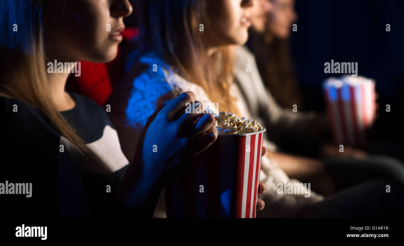 Teenager friends at the cinema watching a movie together and eating popcorn, beautiful girl on foreground, movies - Stock Image