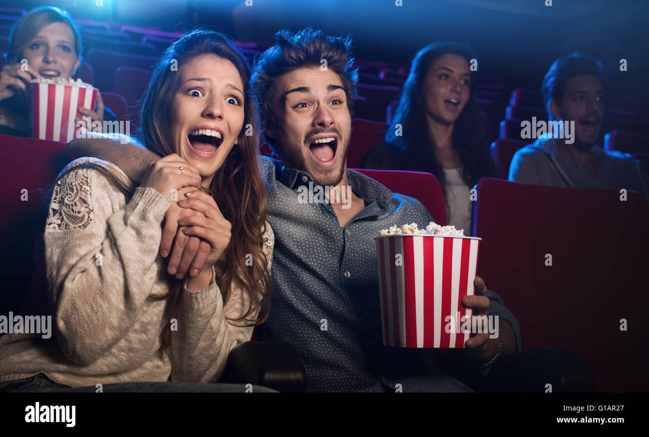Young scared couple at the cinema watching an horror movie and screaming, she is holding her boyfriend's hand - Stock Image