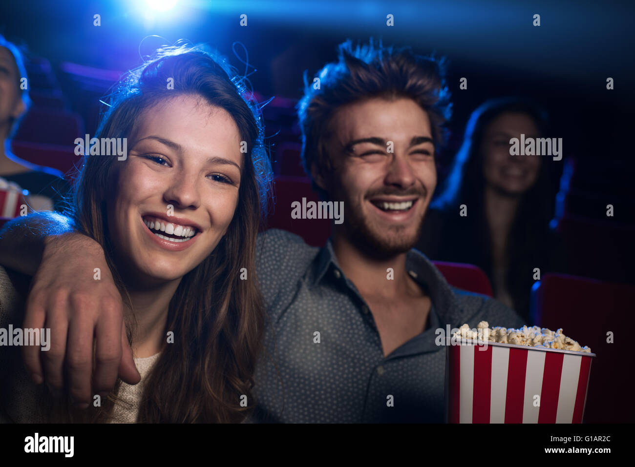 Happy young couple in the movie theater watching a film and smiling, entertainment and togetherness concept - Stock Image