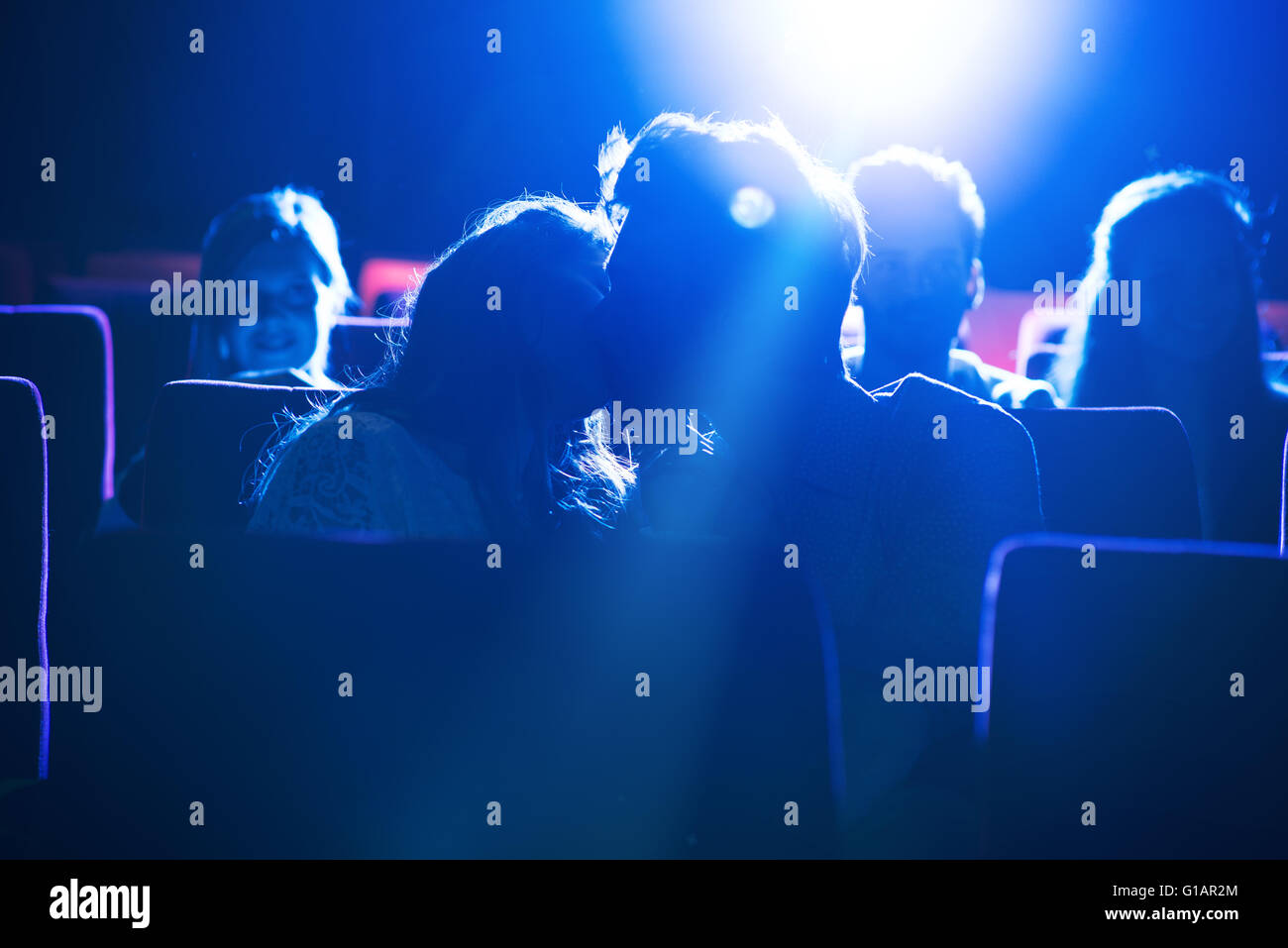 Romantic loving couple kissing at the cinema, love and relationships concept - Stock Image