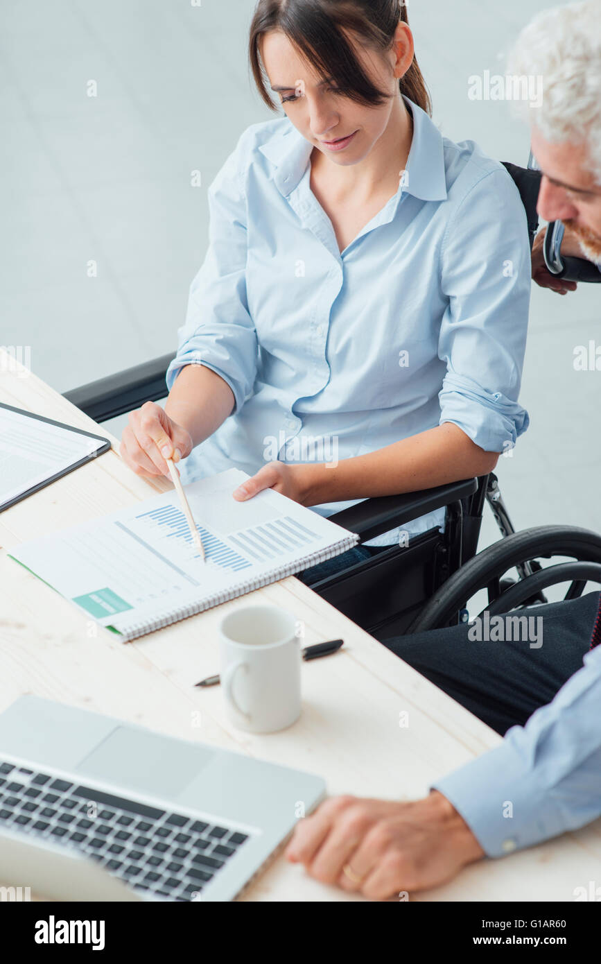 Young business woman on wheelchair working at office desk and checking paperwork with her male colleague, disability - Stock Image