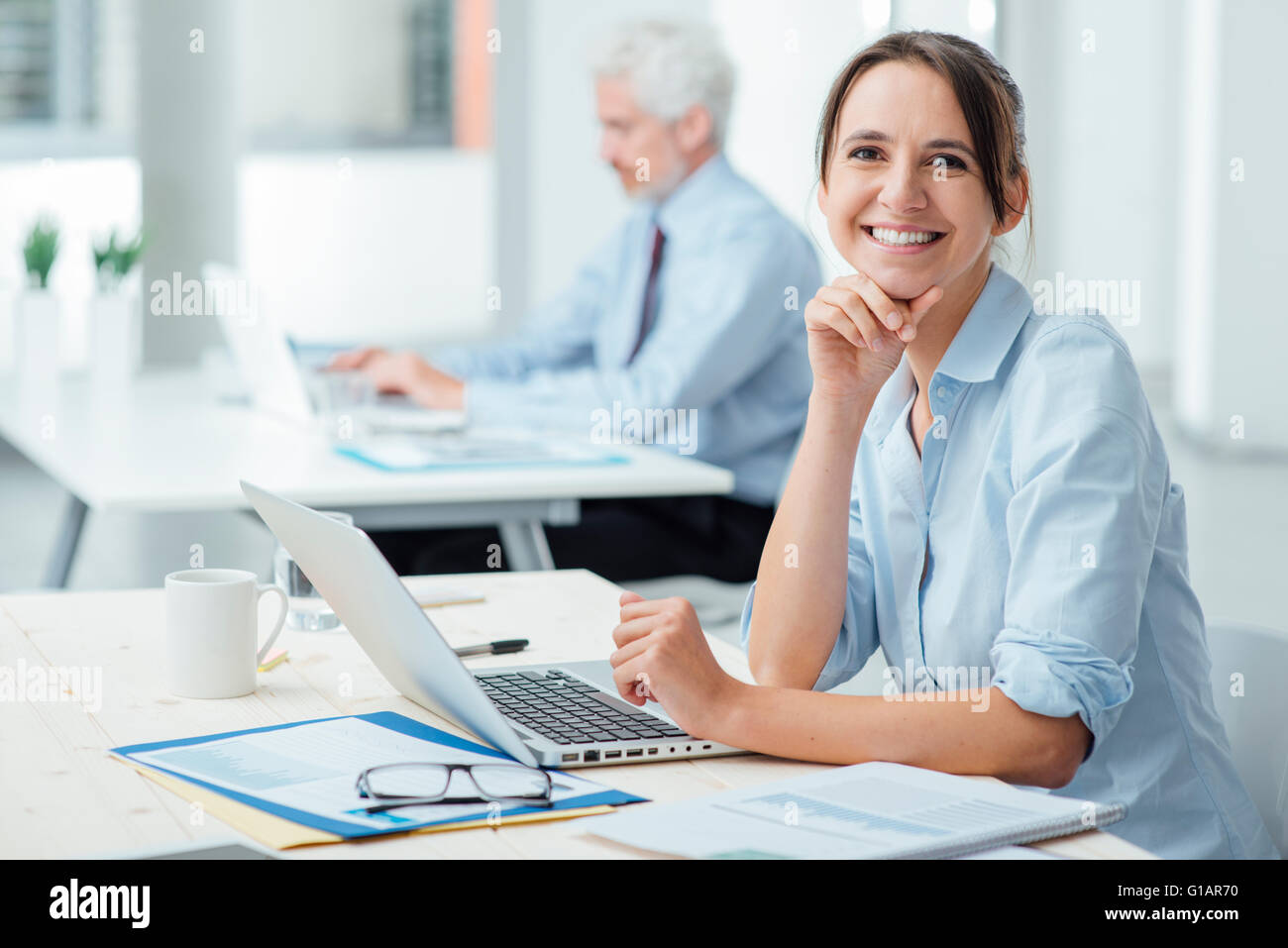 Smiling young business woman sitting at office desk and working with a laptop, she is looking at camera - Stock Image