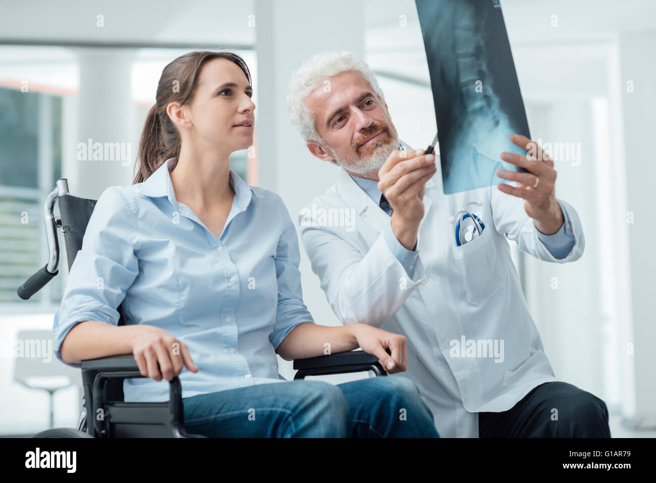 Radiologist examining a woman in wheelchair's x-ray of human spine during a visit at hospital - Stock Image