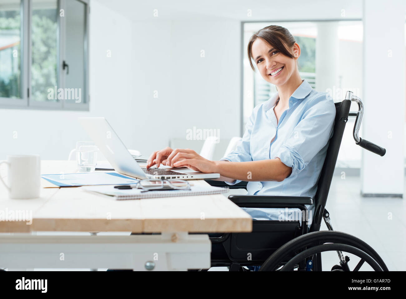 Confident happy businesswoman in wheelchair working at office desk and using a laptop, she is smiling at camera, - Stock Image