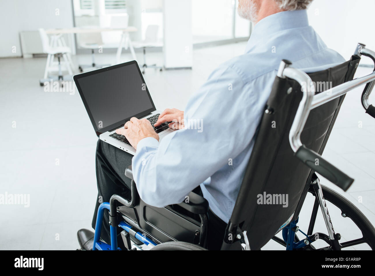 Corporate businessman in wheelchair using a laptop and networking, unrecognizable person - Stock Image