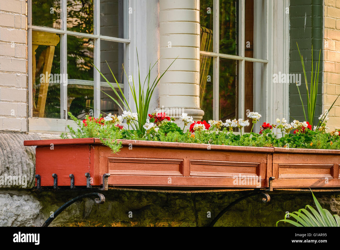 Old window box with geraniums on a stately Victorian home. - Stock Image