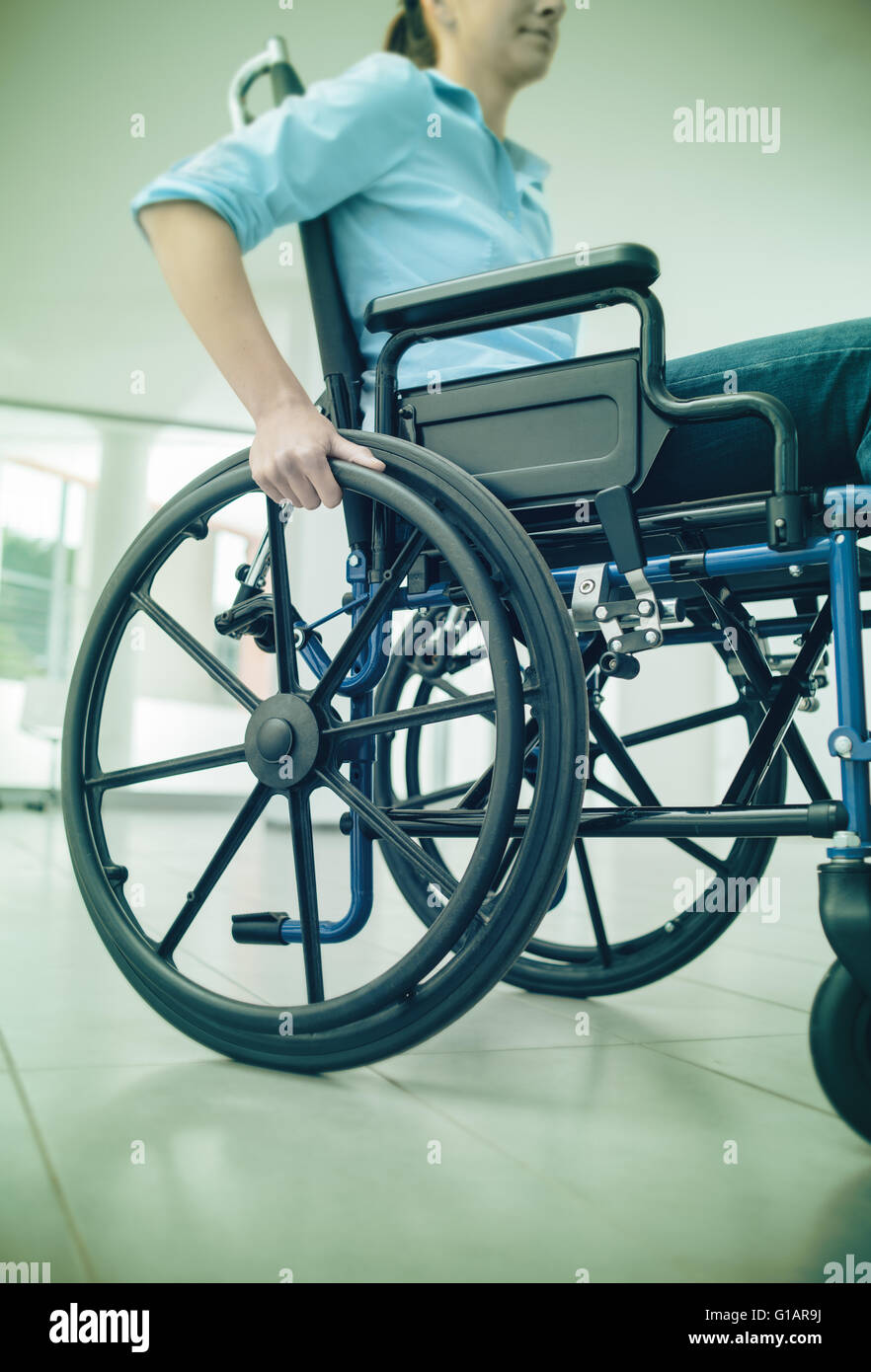 Young woman in wheelchair hand pushing on wheel close up, disability and handicap concept - Stock Image