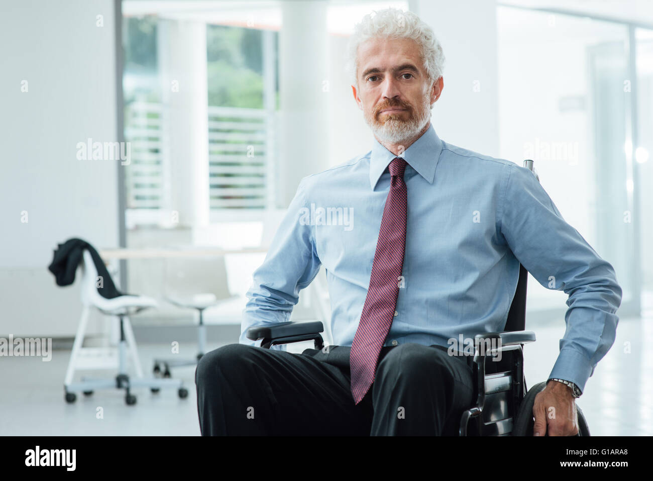 Successful confident businessman in wheelchair smiling at camera, career and disability overcoming concept - Stock Image