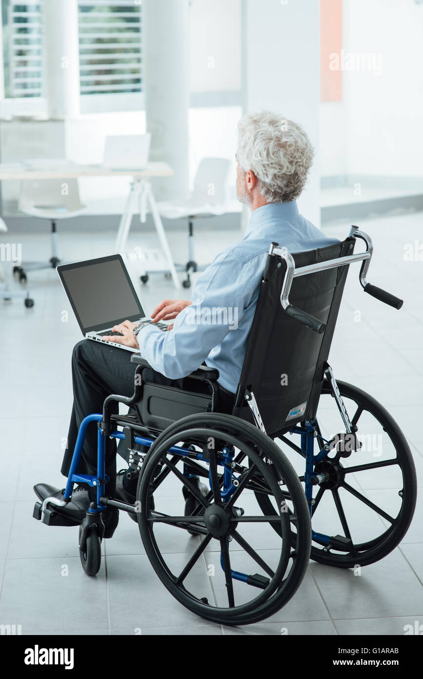 Successful corporate businessman in wheelchair at office using a laptop and working - Stock Image