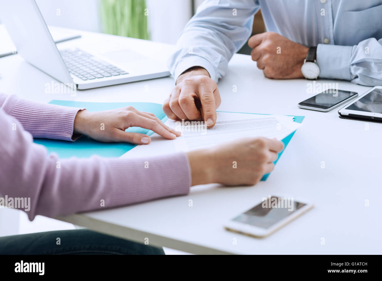 Young woman having a business meeting with an executive in his office, he is pointing on a contract and giving explanations - Stock Image