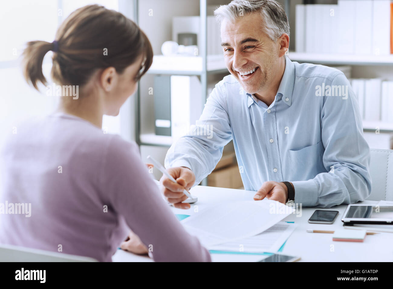Young woman having a business meeting and signing a contract, recruitment and agreement concept - Stock Image