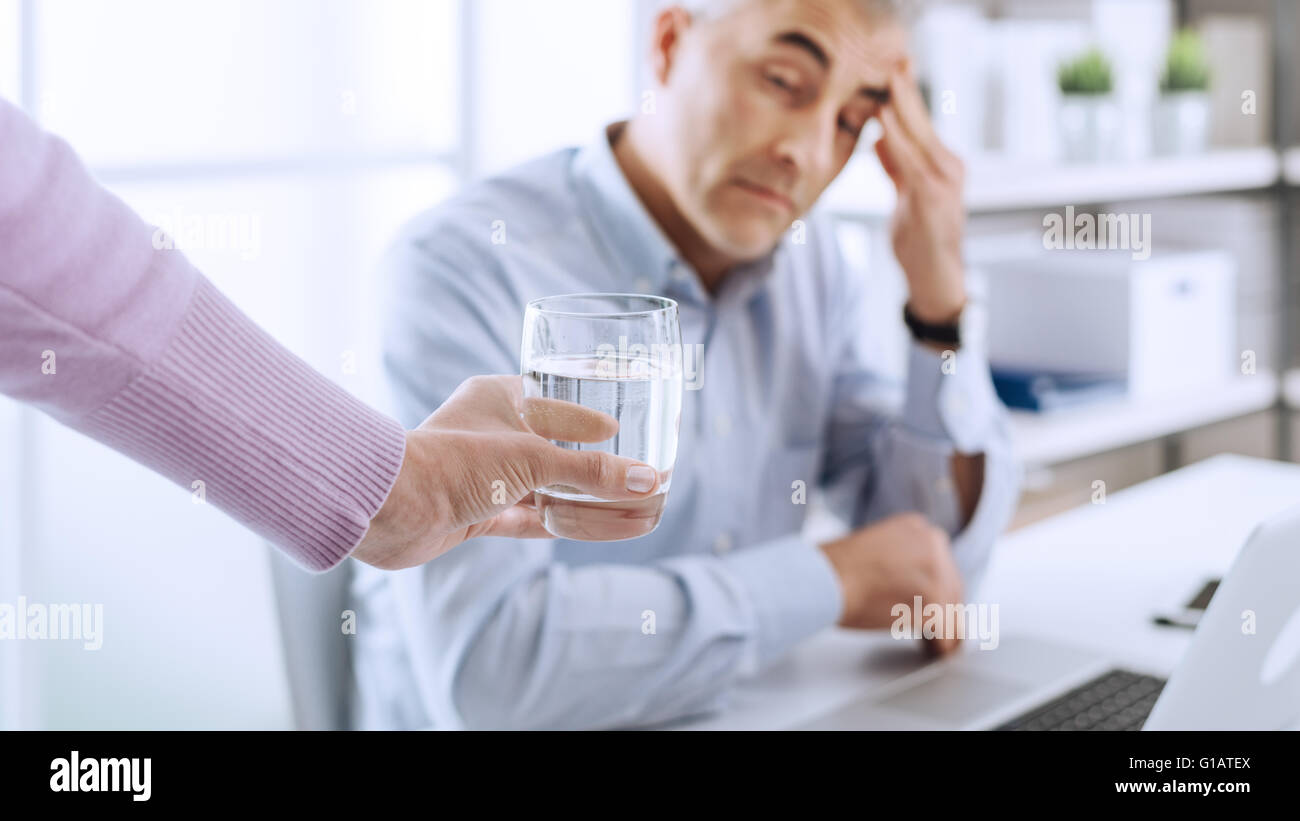 Tired businessman in the office working at desk and having a bad headache, his colleague is giving him a glass of - Stock Image