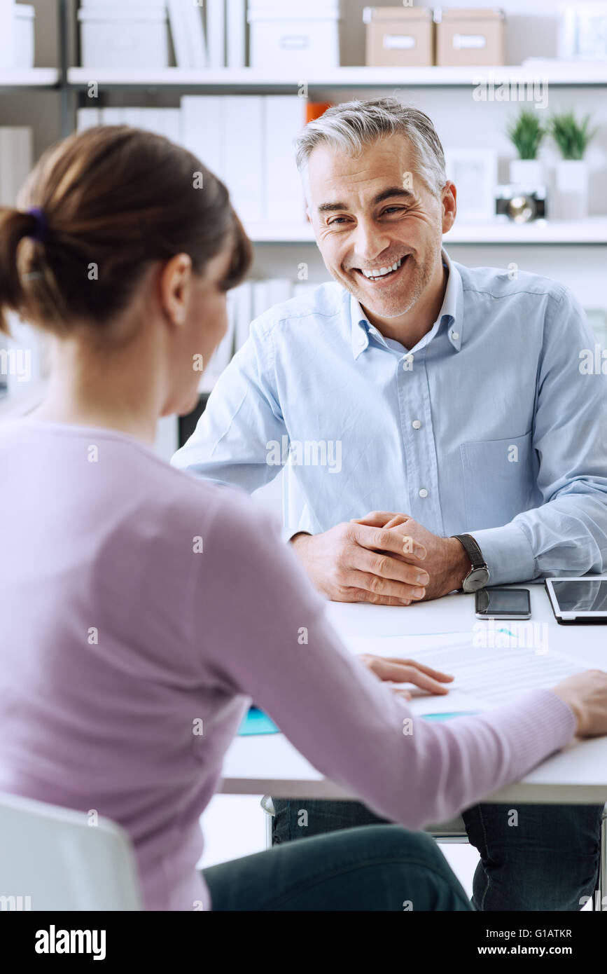 Mature businessman and young woman having a business meeting in the office, they are discussing together - Stock Image