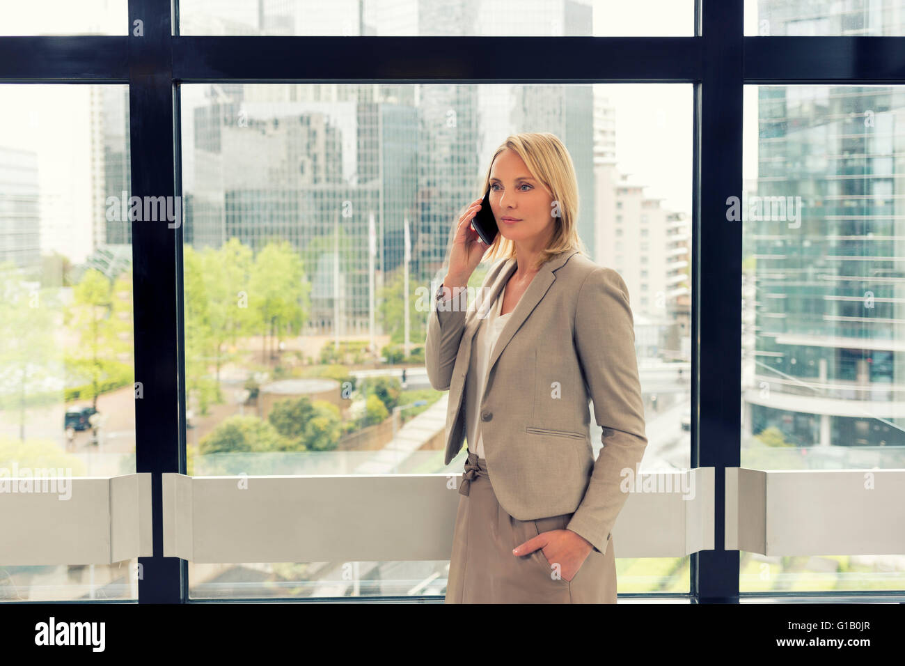 Cheerful business woman on mobile phone at modern office. Buildings background - Stock Image