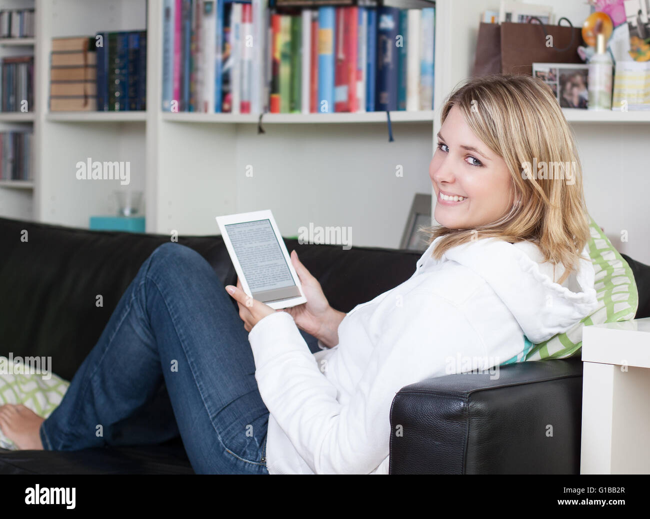 Woman reads an ebook in her free time on the couch at home - Stock Image