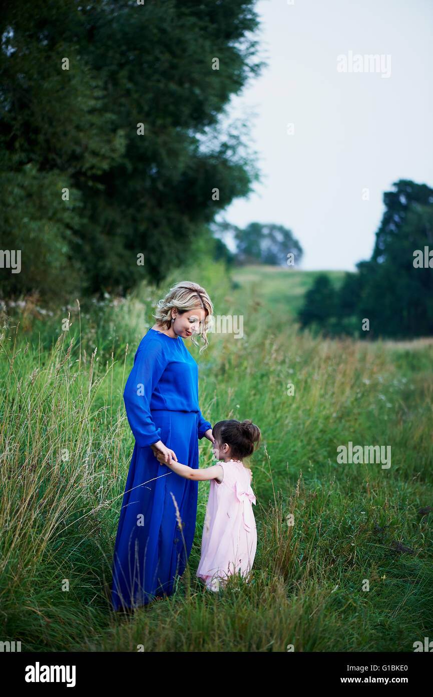 mother and daughter walk along the path among  fields, holding hands - Stock Image