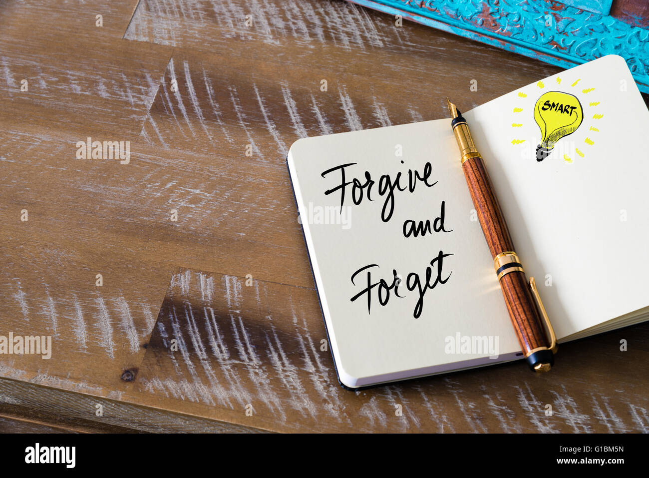 Handwritten text Forgive and Forget with fountain pen on notebook. Concept image with copy space available. - Stock Image