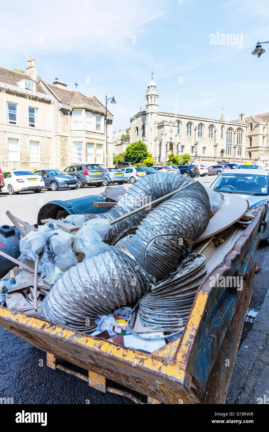 Skip full of rubbish on road builders trash filling skip hire waste management UK England English towns - Stock Image