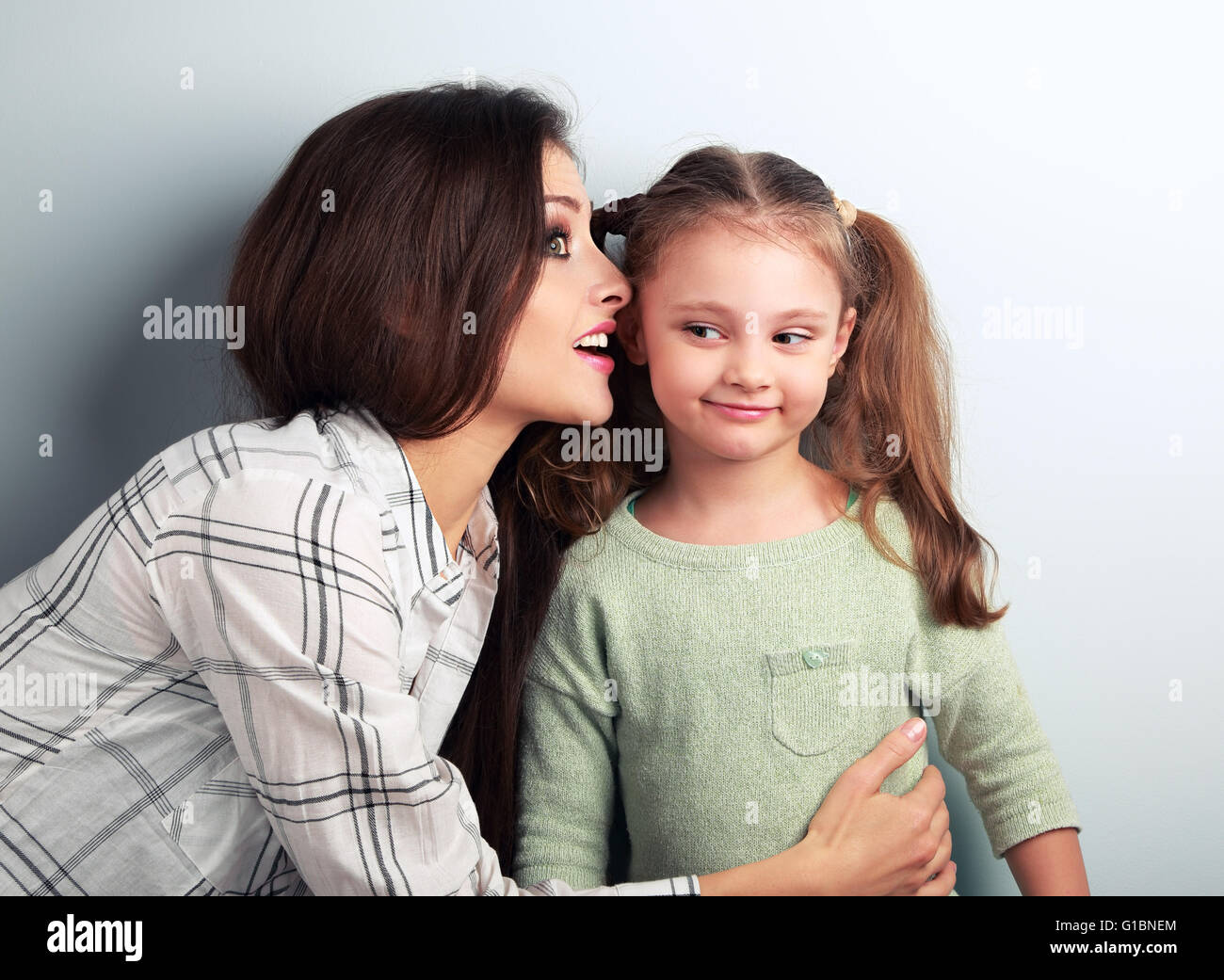 Joying young mother whispering the secret to her funny grimacing daughter in ear in studio - Stock Image