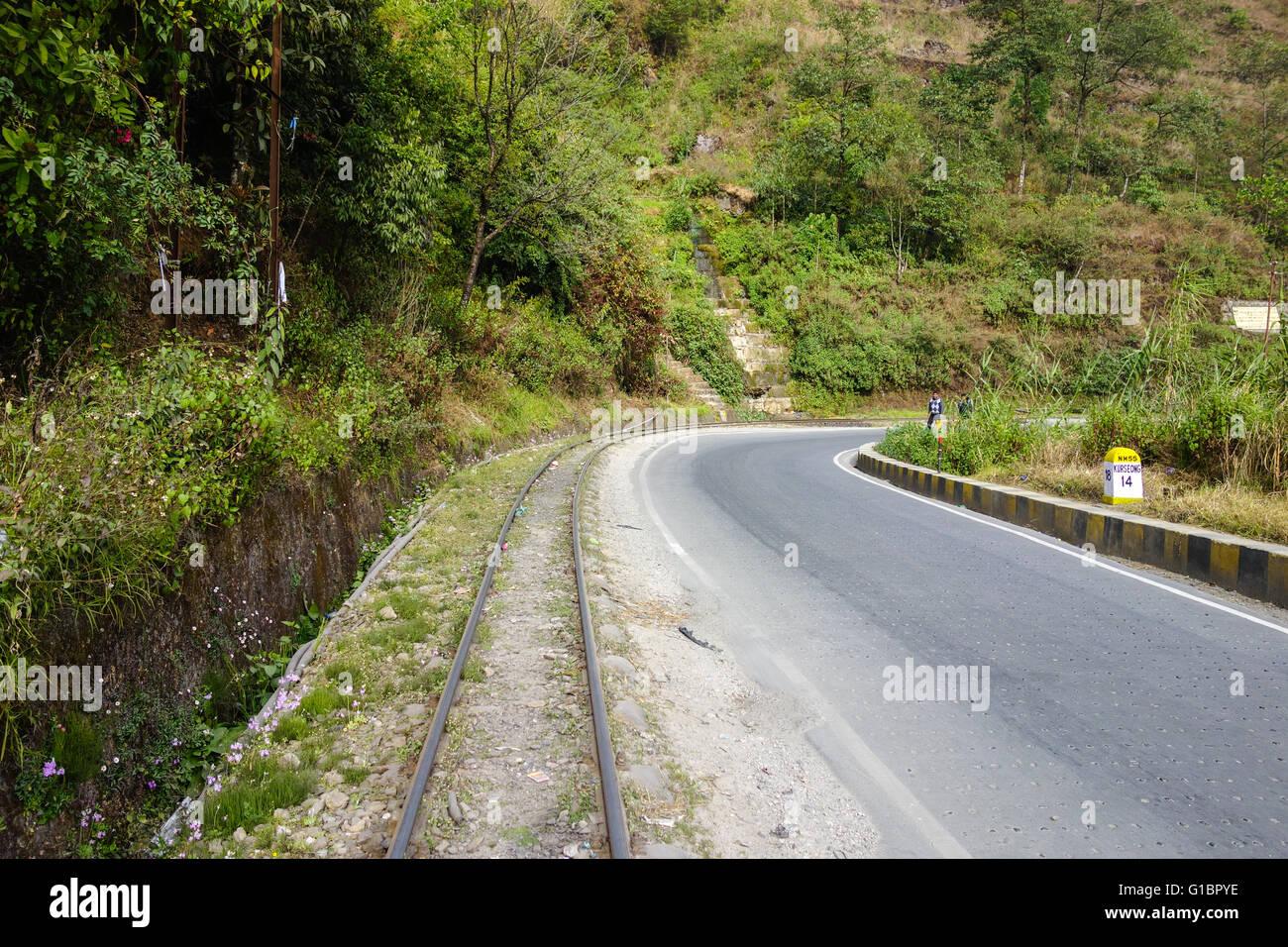 Darjeeling Himalayan Railway Toy Train track alongside National Highway 55 near Sonada, West Bengal, India Stock Photo