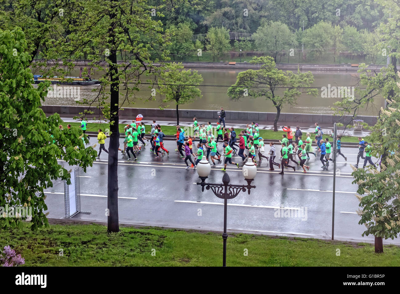 Running adult sportsmens at spring green morning - May 17, 2015, Moscow, Russia, embankment near Moscow-river - Stock Image
