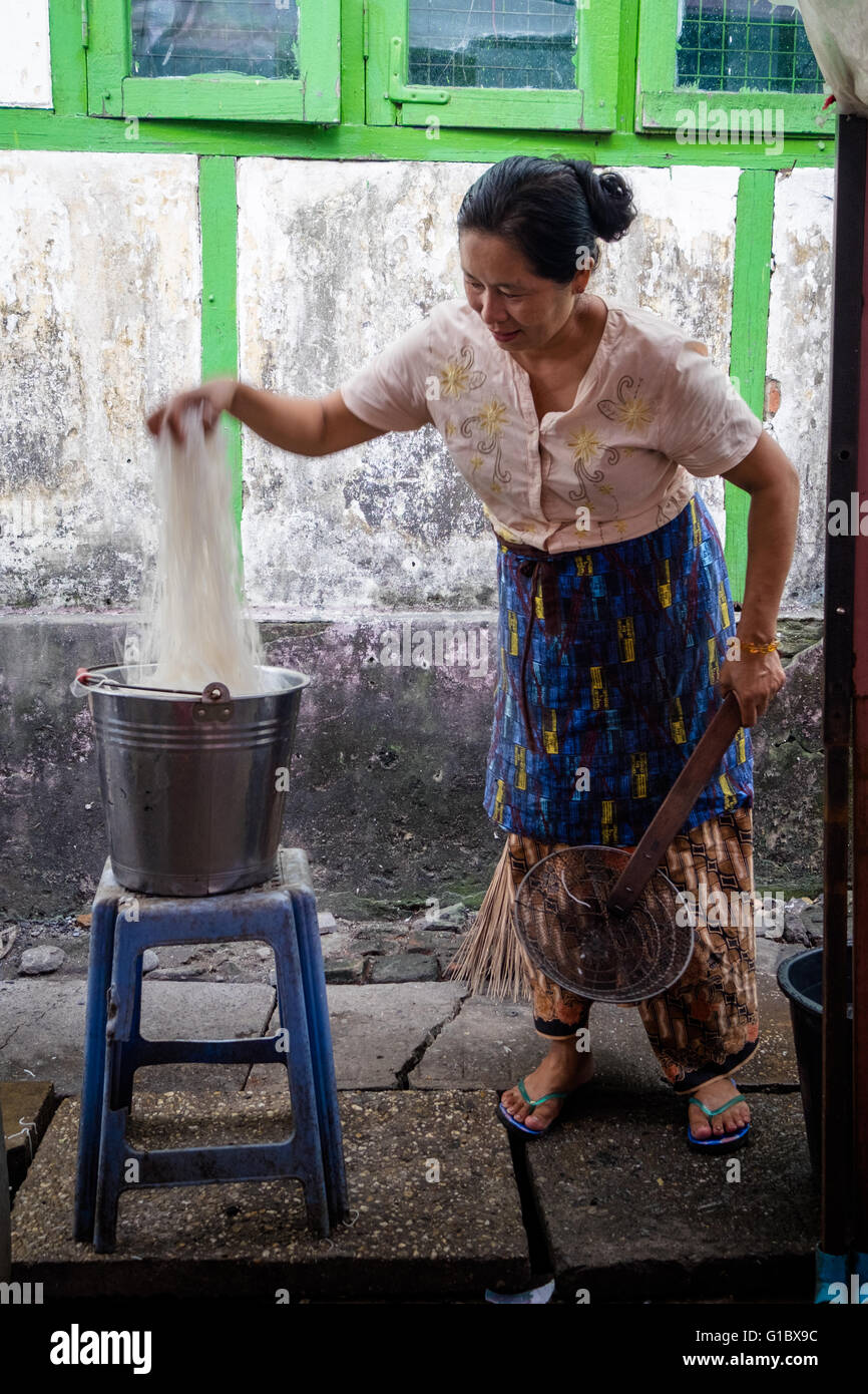 A woman selling noodles at a food stall on 15th Street in Downtown Yangon - Stock Image