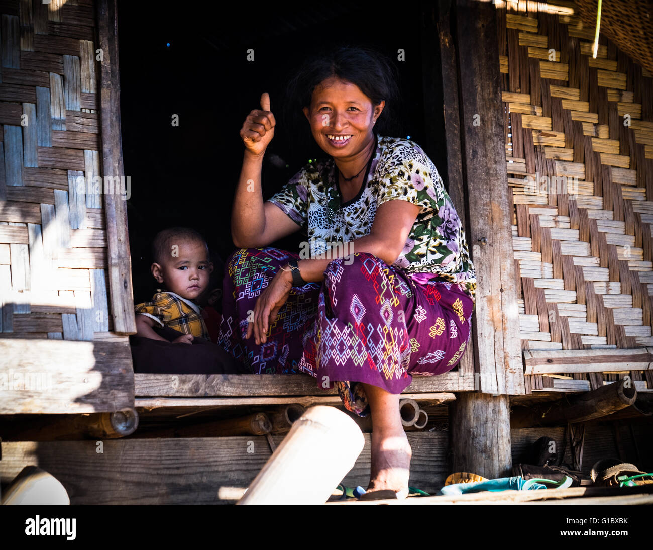A lady and a baby at the entrance to their bamboo house in Pankam Village, near Hsipaw - Stock Image