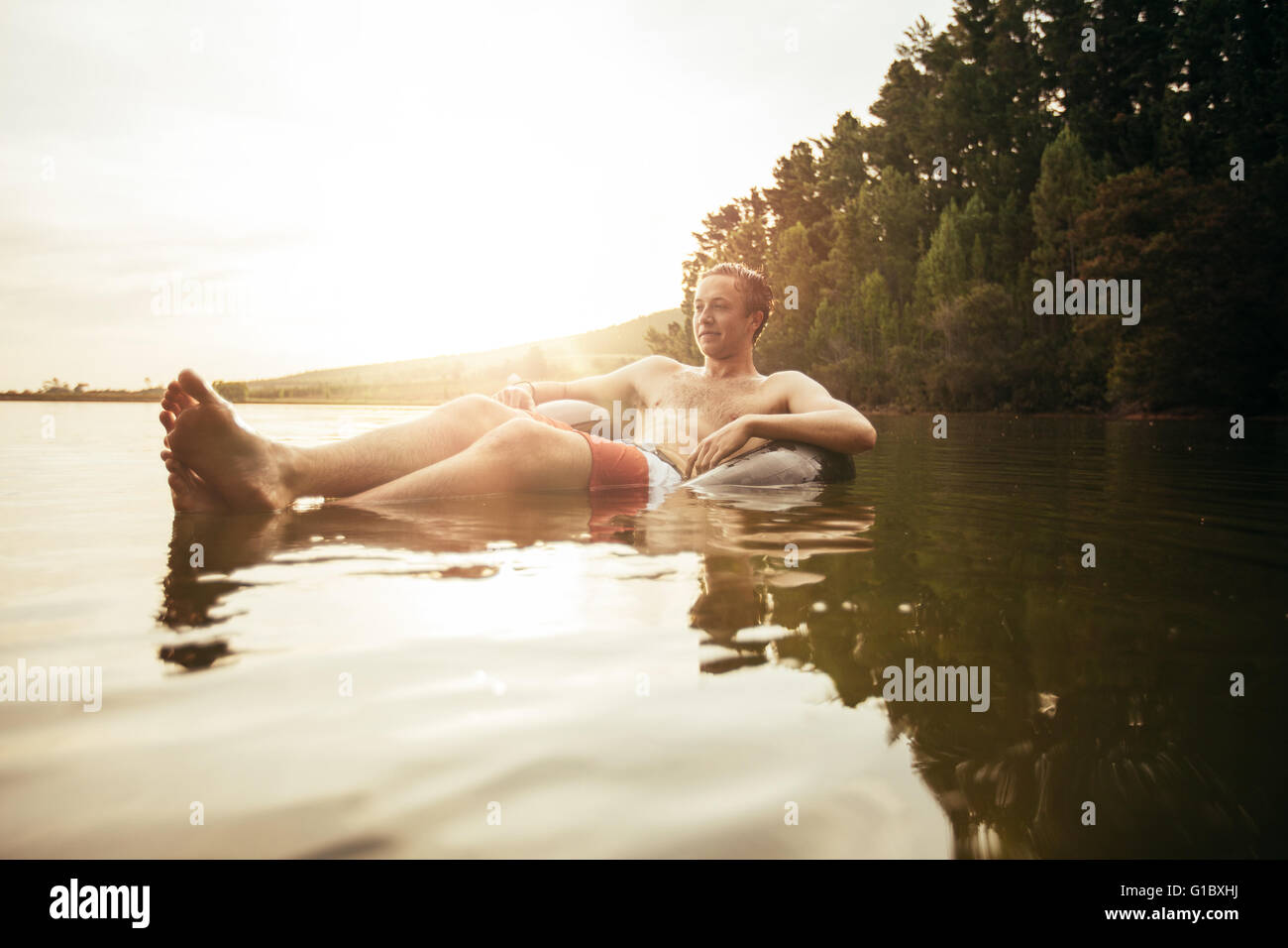 Portrait of young man in lake on inflatable ring. Man relaxing in water on a summer day. - Stock Image