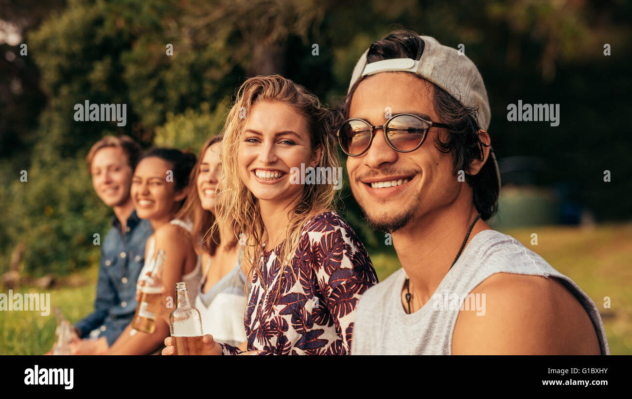 Portrait of young people sitting in a row and looking at camera. Group of friends sitting by a lake and relaxing. - Stock Image