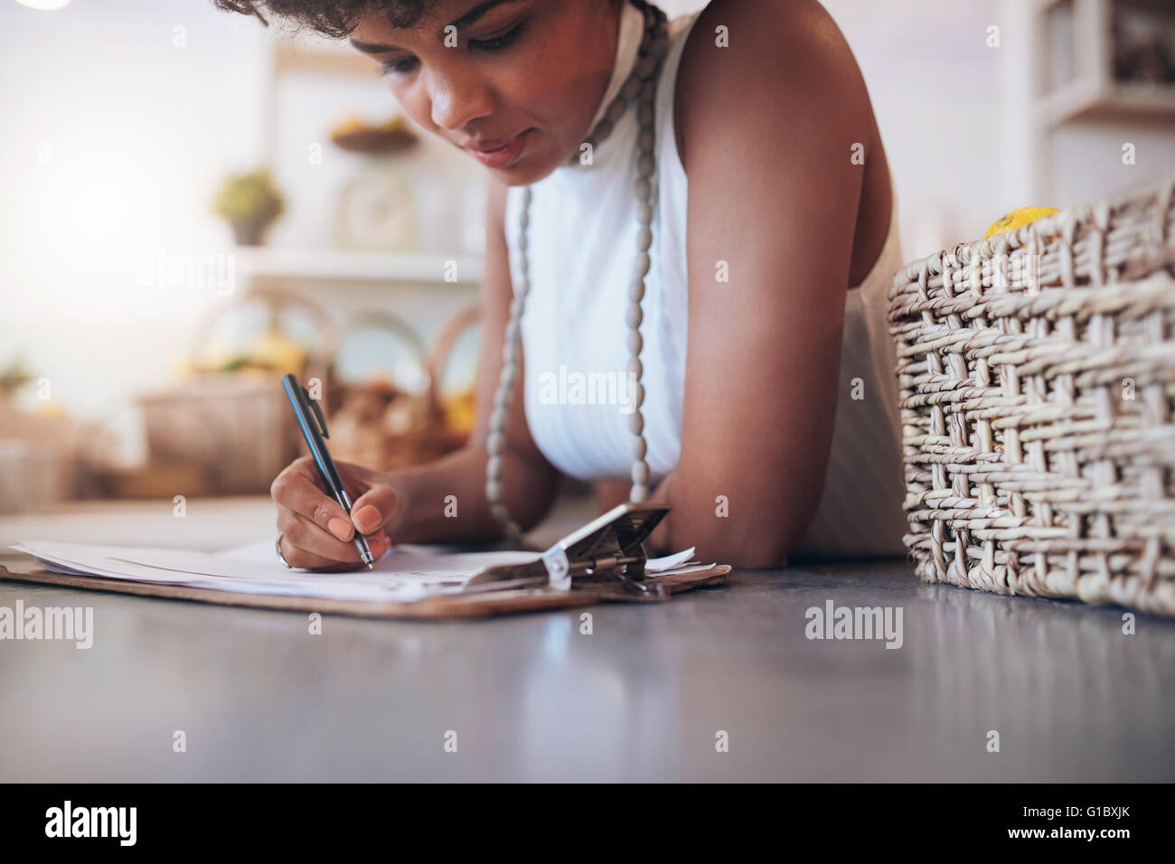 Cropped image of young african woman working in a juice bar. Female standing behind the counter and writing notes. - Stock Image