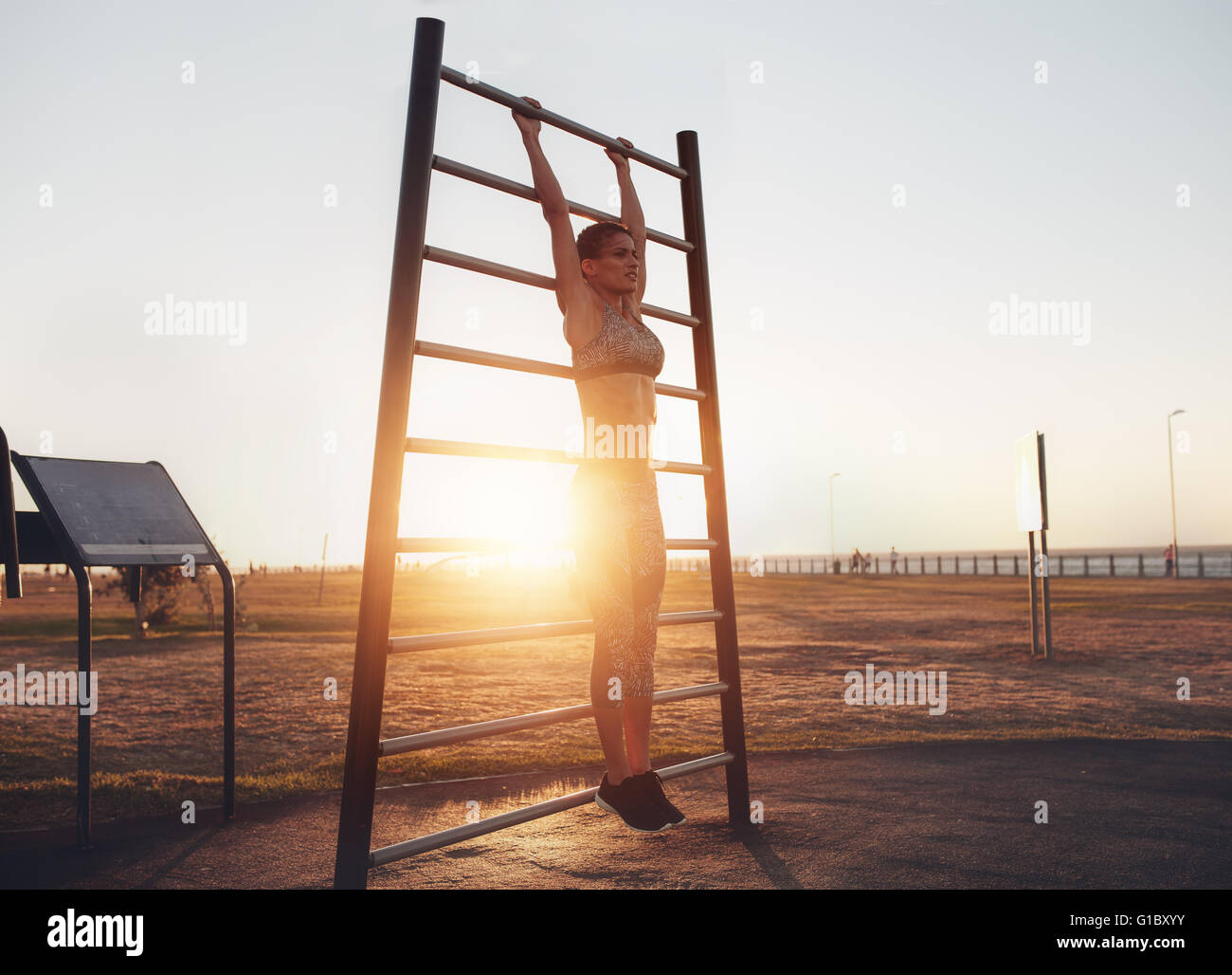Full length shot of fit young woman in sportswear exercising on wall bars outdoors during sunset. Fitness woman - Stock Image